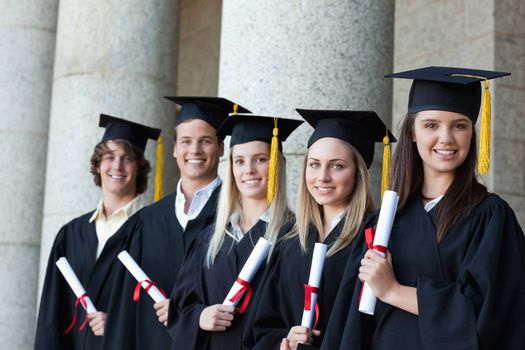 Graduates posing in single line with columns in background