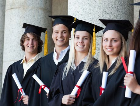 Portrait of smiling graduates posing in single line with columns in background