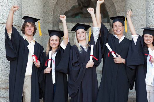 Smiling graduates posing while raising arms in front of the university