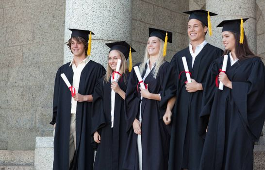 Smiling graduates posing while holding their diploma in front of the university