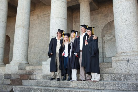 Five graduates posing while holding their diploma in front of the university