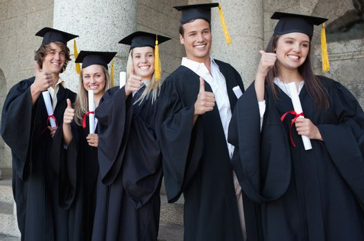 Graduates posing the thumb-up in front of the university