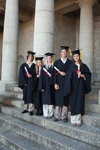 Laughing graduates posing the thumb-up in front of the university