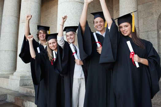 Five happy graduates posing the arm raised in front of the university