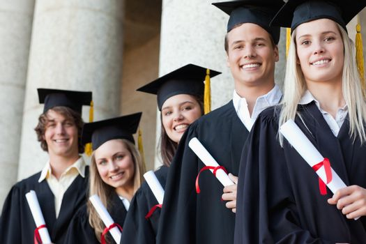 Close-up of five graduates posing in front of the university