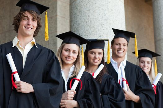 Close-up of five graduates students posing in front of the university