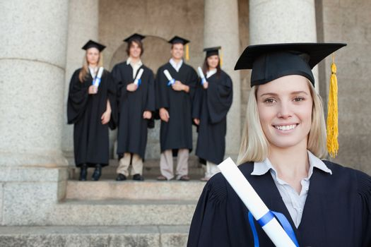 Close-up of a blonde graduate with her friends in background in front of the university