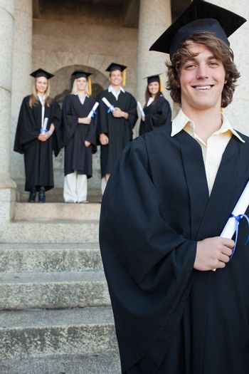 Close-up of a handsome graduate smiling with her friends in background in front of the university