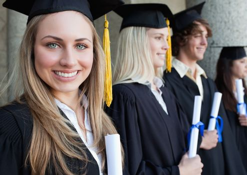 Close-up of a beautiful graduate with blue eyes next to her friends posing