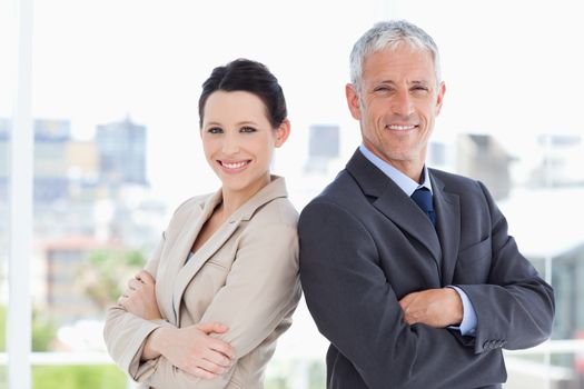 Mature businessman and his secretary standing upright side by si
