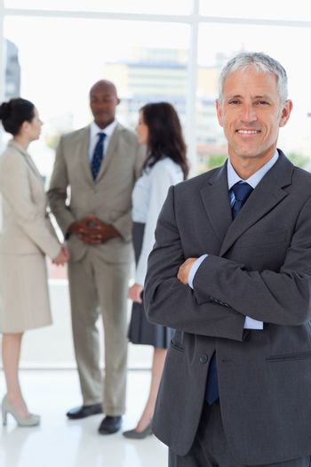 Mature smiling businessman crossing his arms in front of his col