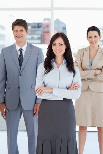 Young businesswoman crossing her arms in front of two relaxed co