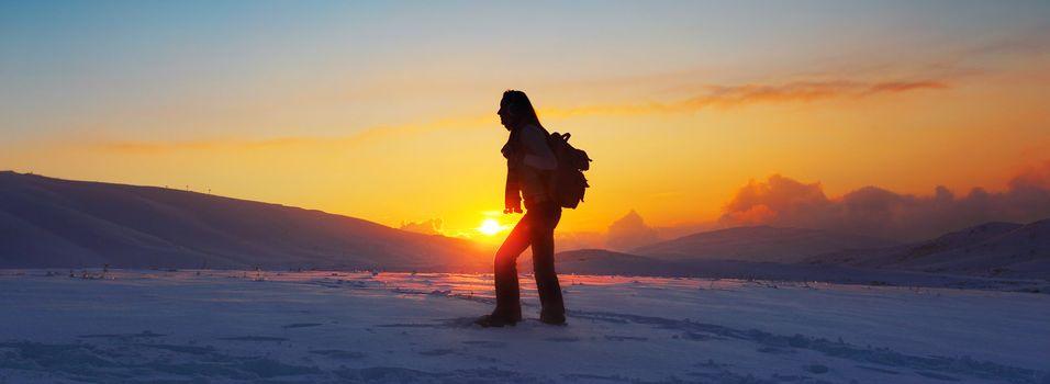 Woman traveler hiking in winter mountains