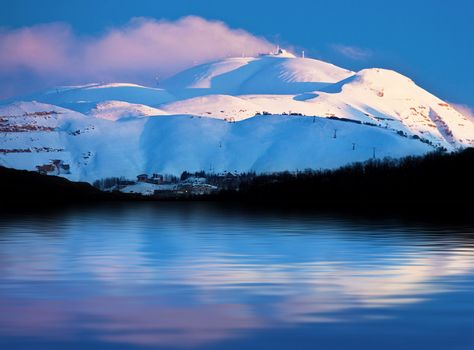 Winter landscape of high mountains covered with snow reflected in fresh lake water, pink sunset over clear blue sky, beautiful seasonal nature,  panoramic wintertime image, cold weather