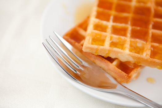 Two waffles and a fork on a saucer