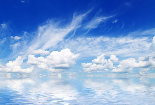 white fluffy clouds with rainbow in the blue sky