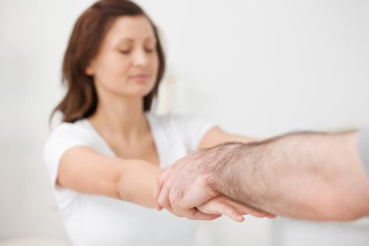 Practitioner extending the arms of a patient