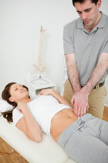 Physiotherapist touching the abdomen of a woman