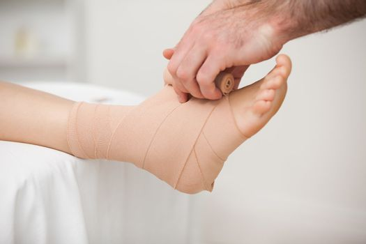 Practitioner bandaging an ankle