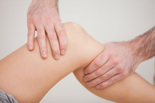 Knee of a patient being touched by a practitioner