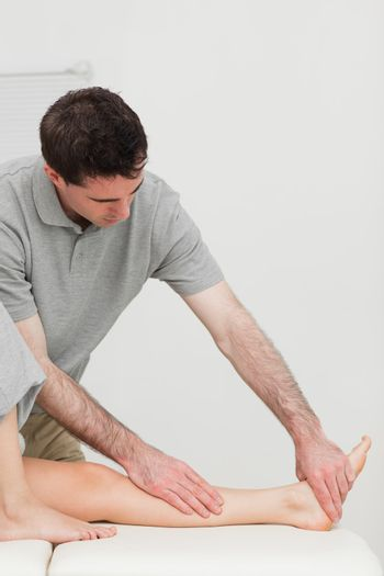 Serious physiotherapist working on the calf of a patient