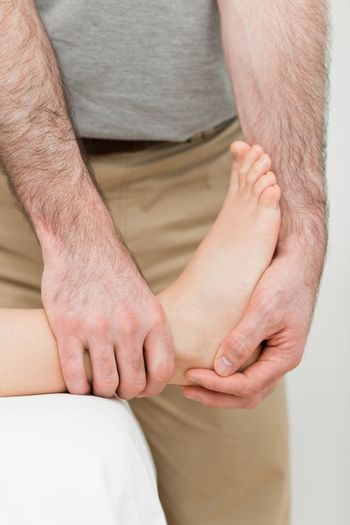 Foot being manipulated by a practitioner