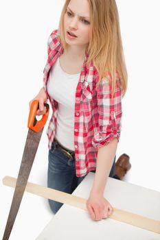 Woman using a wood saw