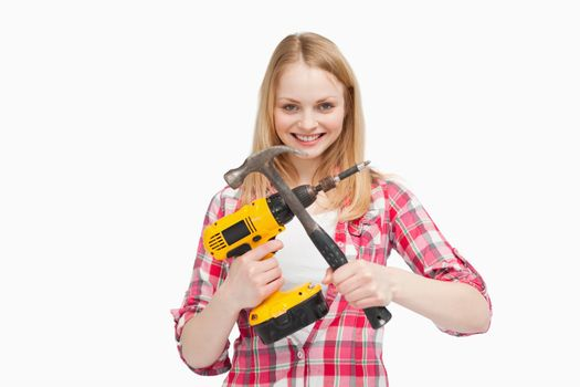Woman holding an electric screwdriver and a hammer