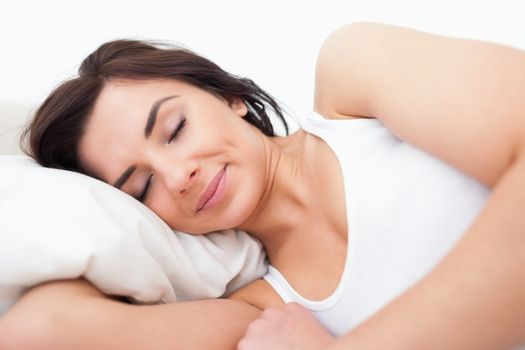 Peaceful woman lying while sleeping in the morning in her bedroom