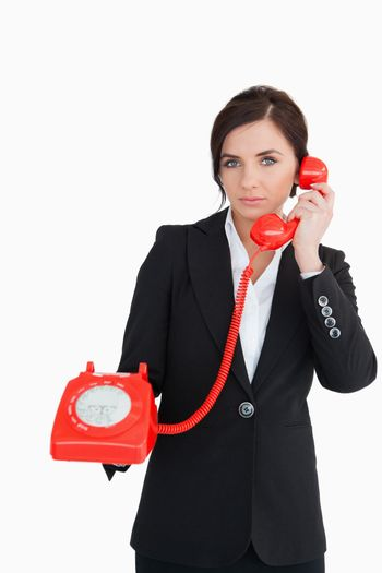 Businesswoman using a red dial telephone