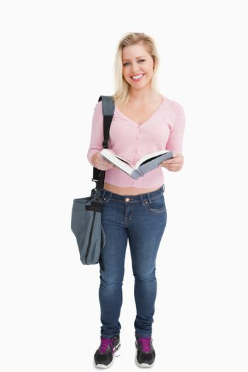 Happy woman standing while holding a novel