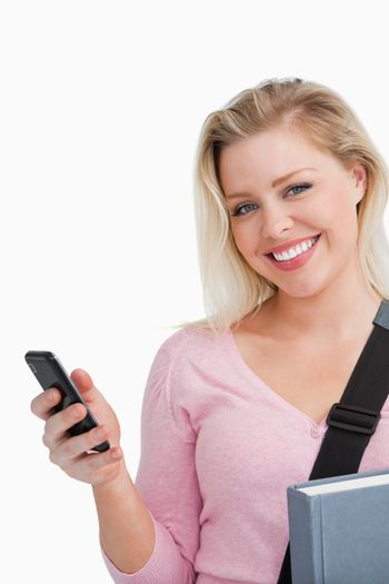 Smiling woman holding her cellphone and a novel