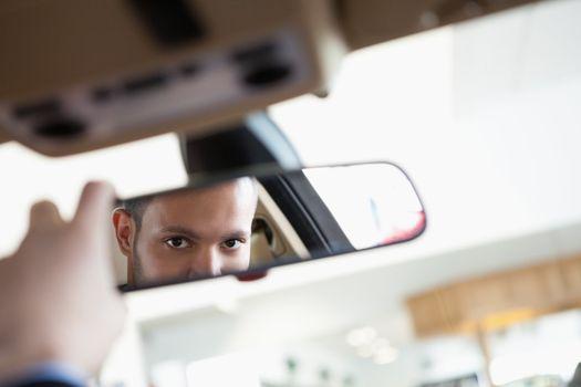 Man looking in an interior car mirror