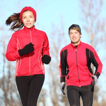 Healthy lifestyle winter running. Runner couple jogging in city park in warm winter sports clothing. Fit Asian woman fitness model and Caucasian man model.