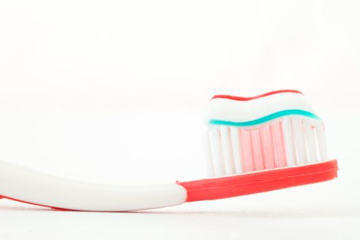 Toothpaste on a red toothbrush