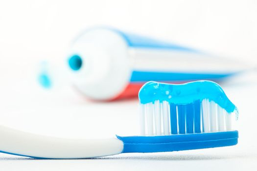 Toothbrush with blue toothpaste next to a tube of toothpaste