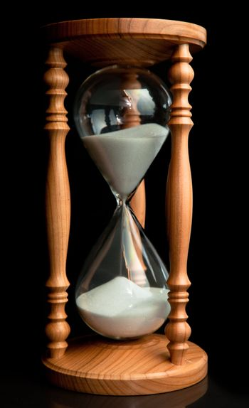 Sand flowing inside of hourglass