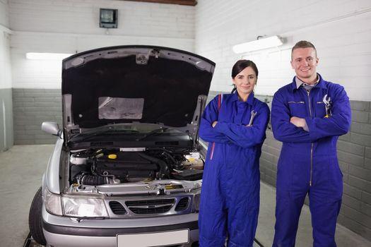 Mechanics next to a car