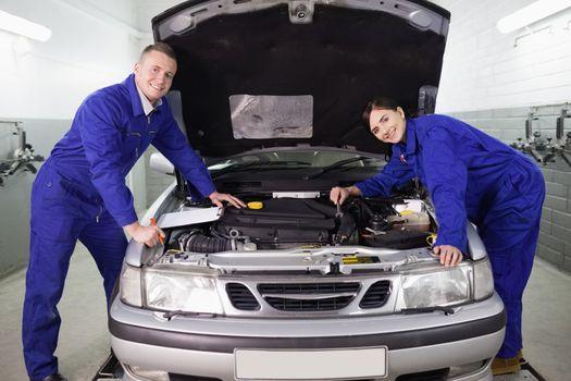 Mechanics leaning on a car