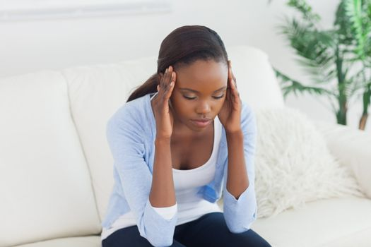 Black woman holding her head in a living room