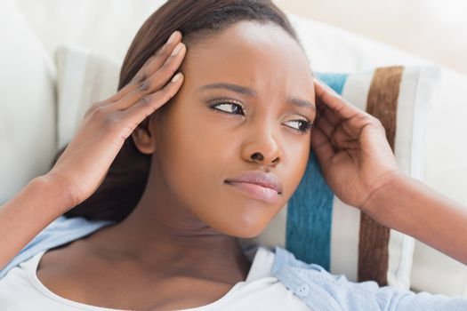 Black woman having pains on the head in a living room