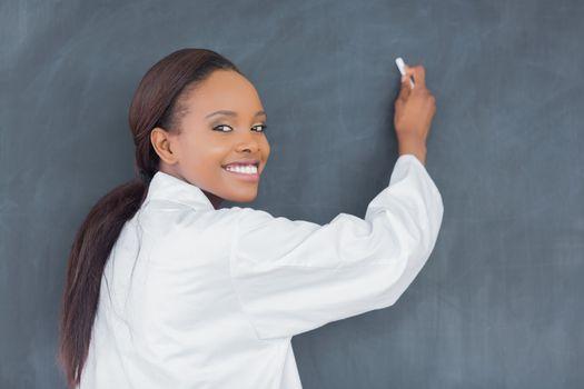 Black teacher holding a chalk in a classroom