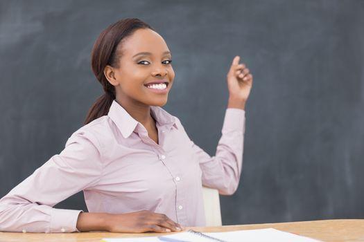 Black teacher showing the blackboard in a classroom