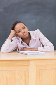 Sad black woman at desk in a classroom