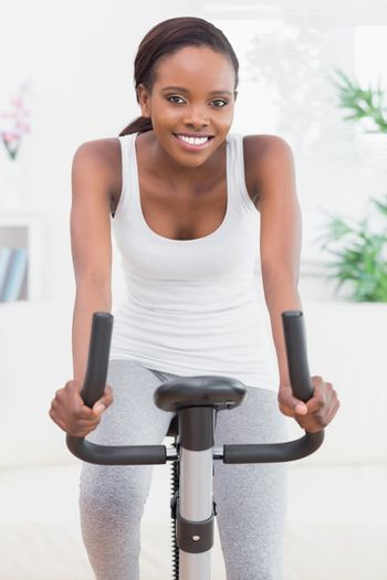 Black woman doing exercise bike in a living room
