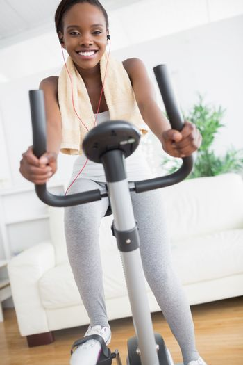 Black woman smiling while doing sport in a living room