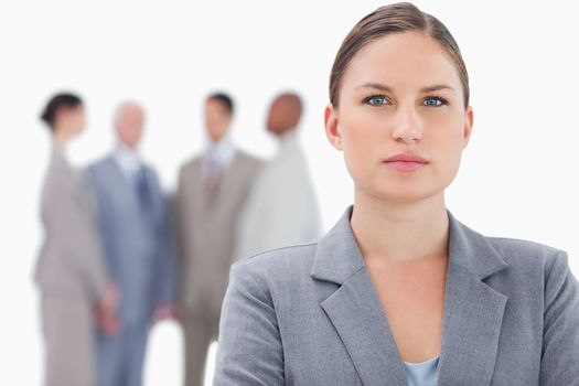 Serious businesswoman with co-workers behind her