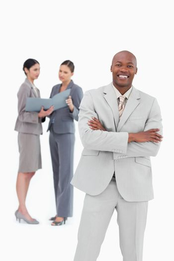 Smiling businessman with co-workers behind him