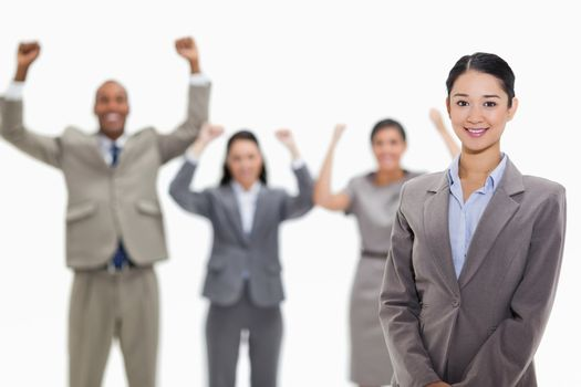 Businesswoman smiling with enthusiastic co-workers