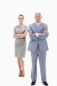 White hair businessman with a woman behind him crossing their ar